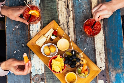 Overhead view of an appetizer platter and hands holding cocktails