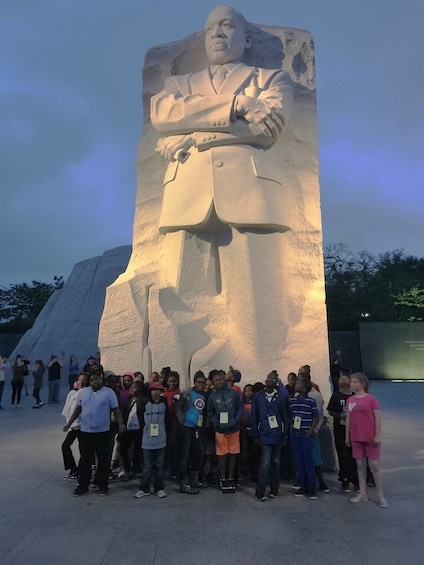 Show item 1 of 6. Group of people pose with a large statue of Martin Luther King Jr. in Washington D.C.