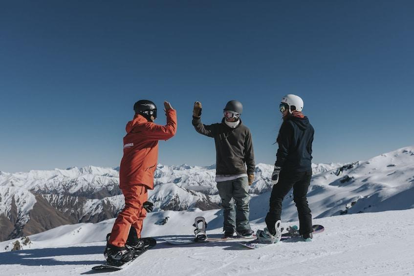 Show item 1 of 4. Snowboarders hi-five on a ski slope