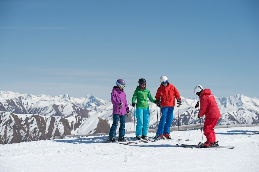 Show item 3 of 4. Skiers pause to look out over a mountain
