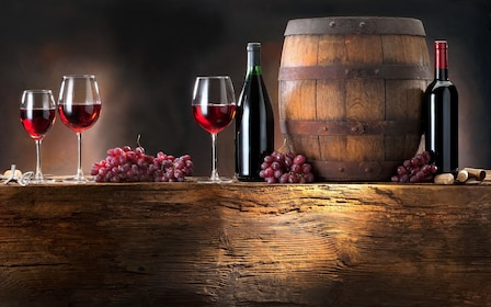 Glasses of wine next to a wine barrel
