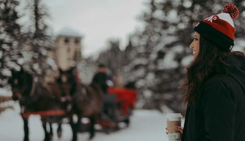 Woman enjoying a cup of coffee outside during the winter time in Banff