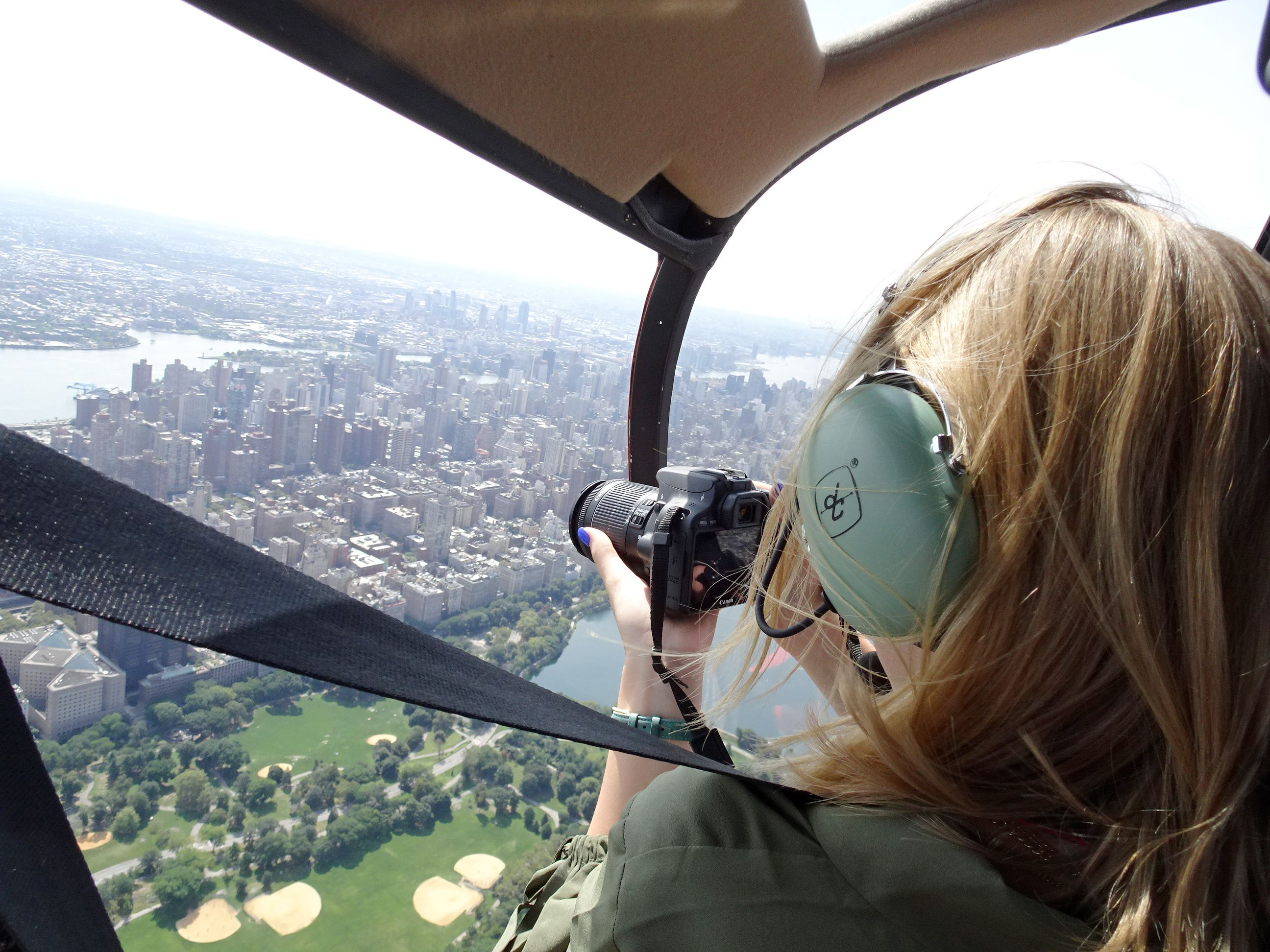Woman taking photos while aboard a helicopter in NYC