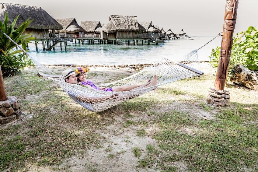 Show item 3 of 5. Couple in a hammock in Mo'orea