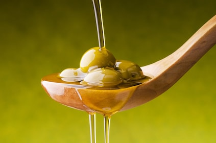Olive oil poured on a spoon with olives