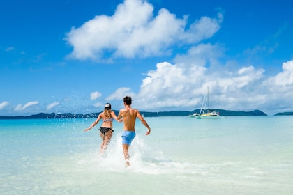 Couple running into crystal clear water on a beach