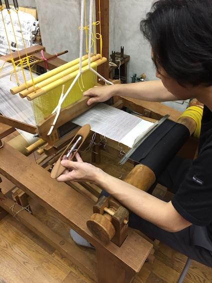 Show item 2 of 6. Woman works on loom to create silk fabric at  Koho Nishiki Textile Studio in Kyoto, Japan