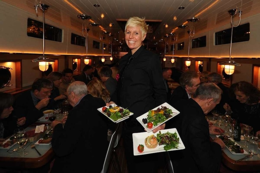 Show item 4 of 7. Server holding plates of food in Canal Boat Restaurant in Dublin's Grand Canal