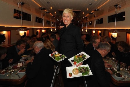 Server holding plates of food in Canal Boat Restaurant in Dublin's Grand Canal
