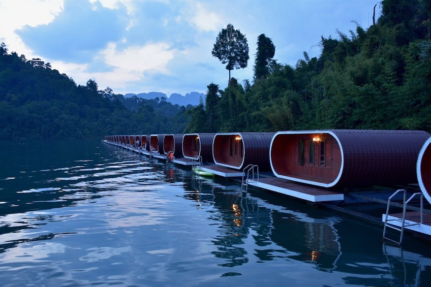 Floating cabins on Cheow Lan Lake at dusk in Thailand