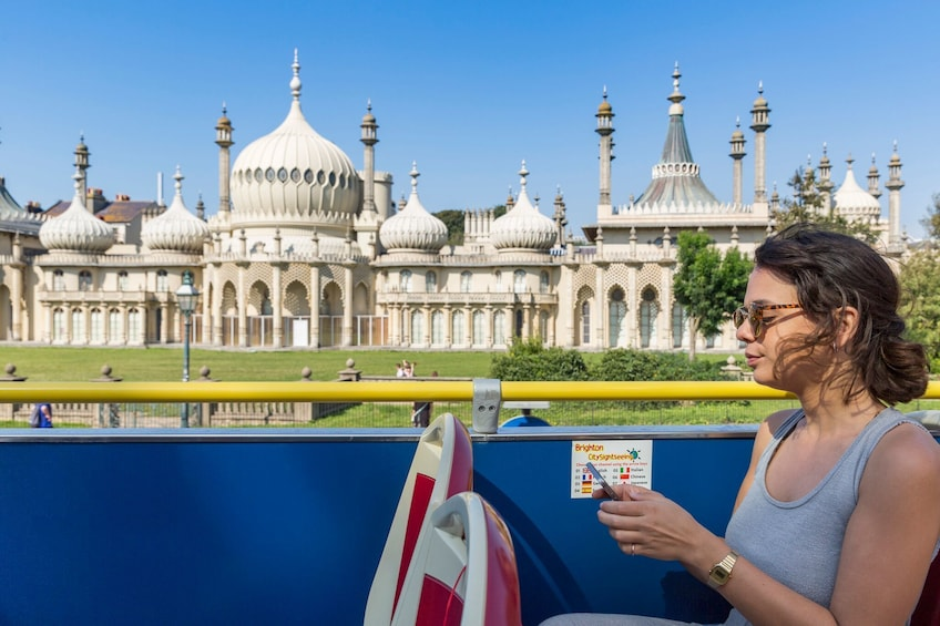 Woman on the double-decker bus in front of the Royal Pavilion in Brighton, England