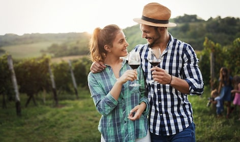 Couple enjoying red wine while walking about a Chianti vineyards