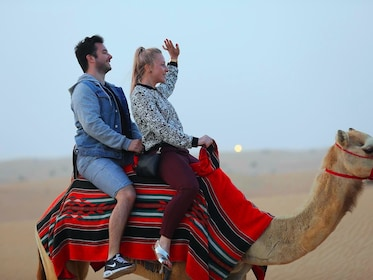 Couple riding a camel in the Lahbab Desert