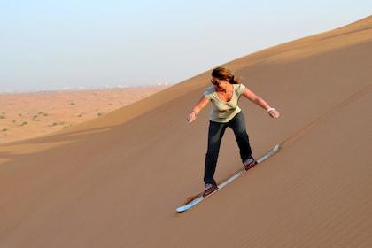 Woman sandboarding in the Lahbab Desert in the morning