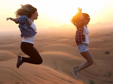 Two women jumping in the Lahbab Desert at sunset