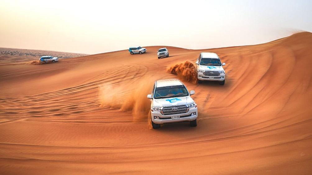 Show item 3 of 10. Dubai Morning Safari: Red Dunes, Sandsurf, Camels & Brunch