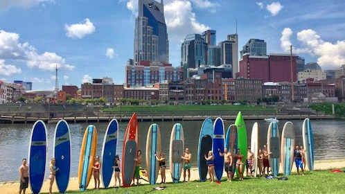 Group of people standing with paddle boards next to a river in Nashville