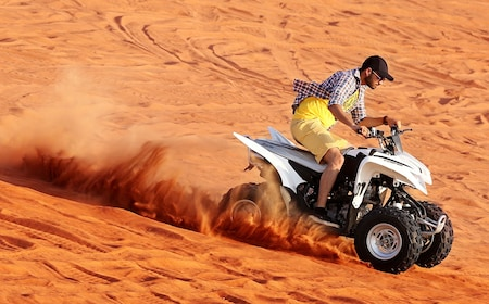 Person riding an ATV on a sand dune