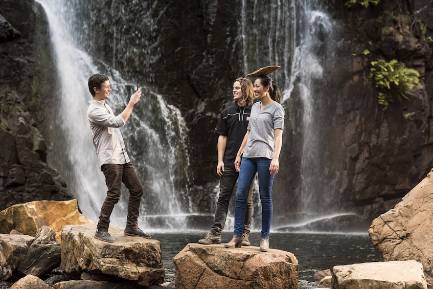 Show item 3 of 10. Couple taking a photo by a waterfall in Australia
