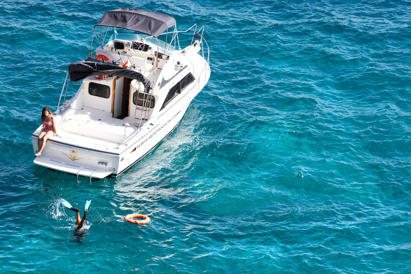 Show item 1 of 6. Guest snorkeling in Tenerife while a woman is sunbathing on a boat