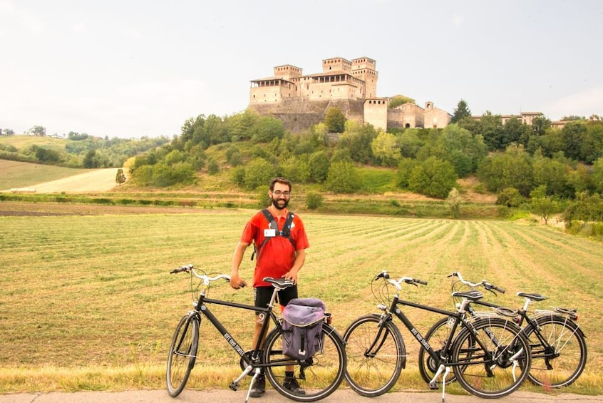 Show item 1 of 6. Man stands with 3 bikes in front of a castle in Parma