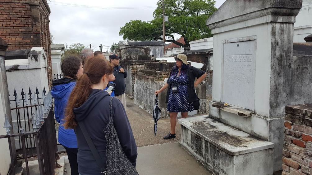 Show item 1 of 5. Tour group with guide at a cemetery in New Orleans