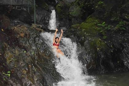 Woman swimming down a waterfall in Herradura