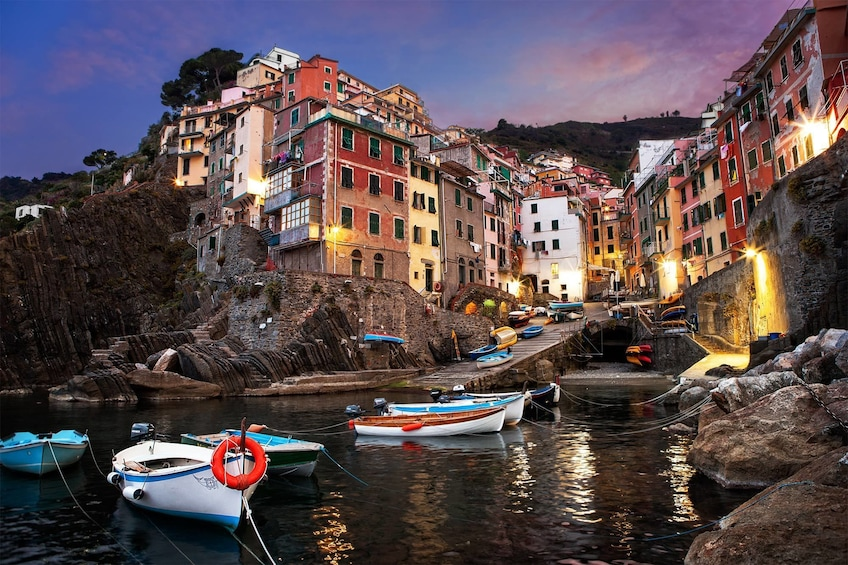 Show item 2 of 5. Boats on a harbor in Cinque Terra at dusk