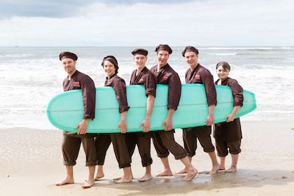 Six people hold a surf board on a beach