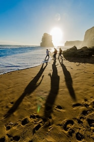 Trio of people walk on the sand in front of the 12 Apostles at sunset