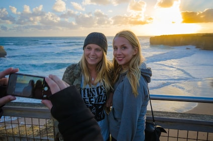 Two women pose for a picture at sunset on the Great Ocean road