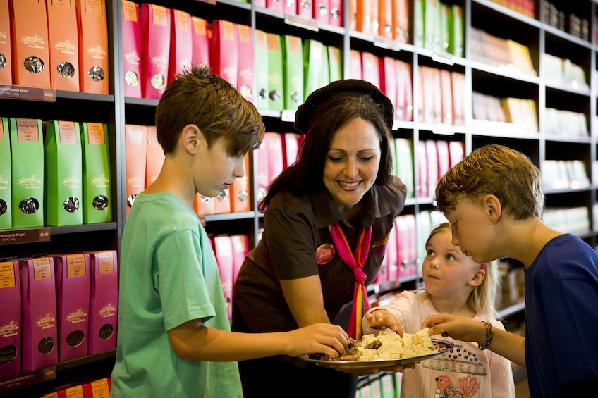Woman and children sample treats at a sweet shop