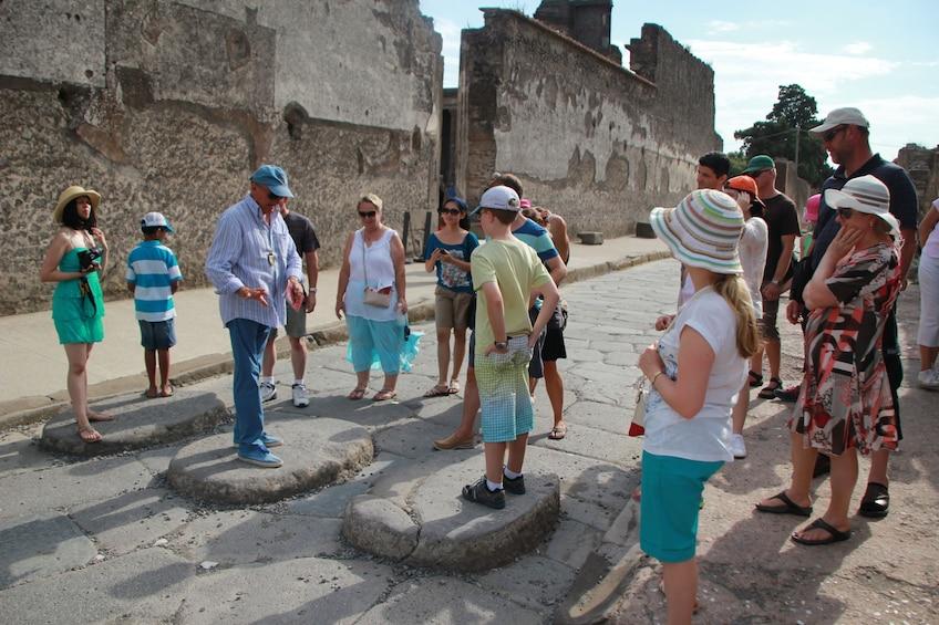 Tourists walk through the ruins of Pompeii