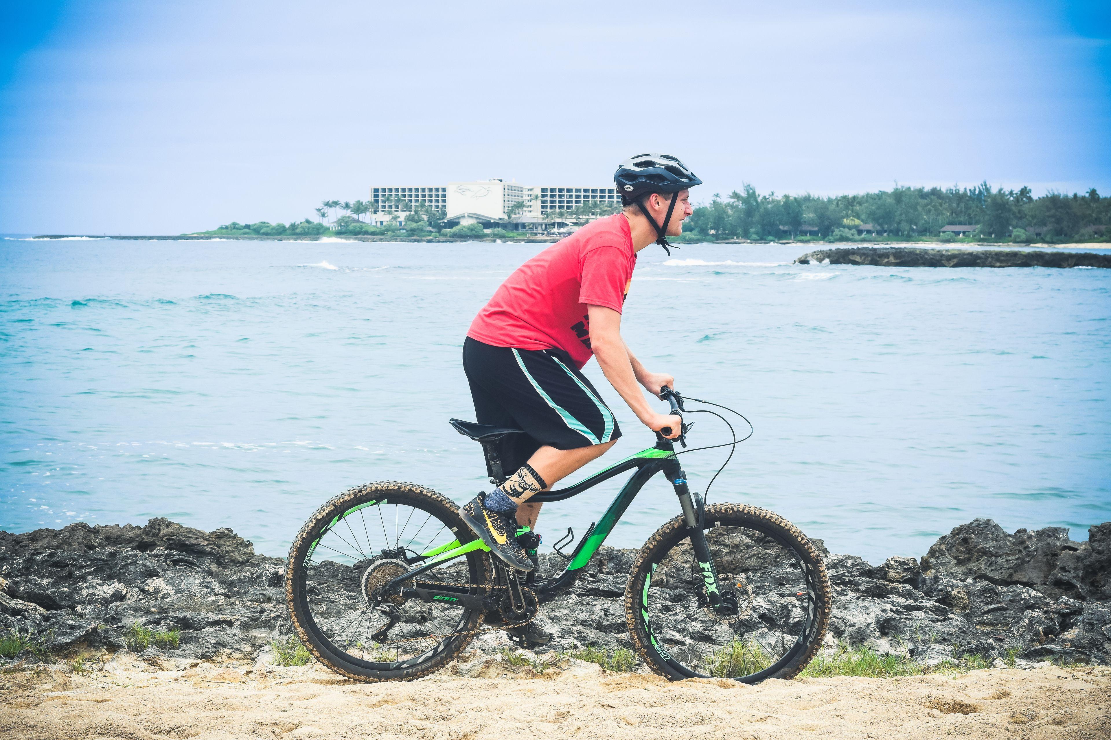 Man bicycling on a coastal path on Oahu