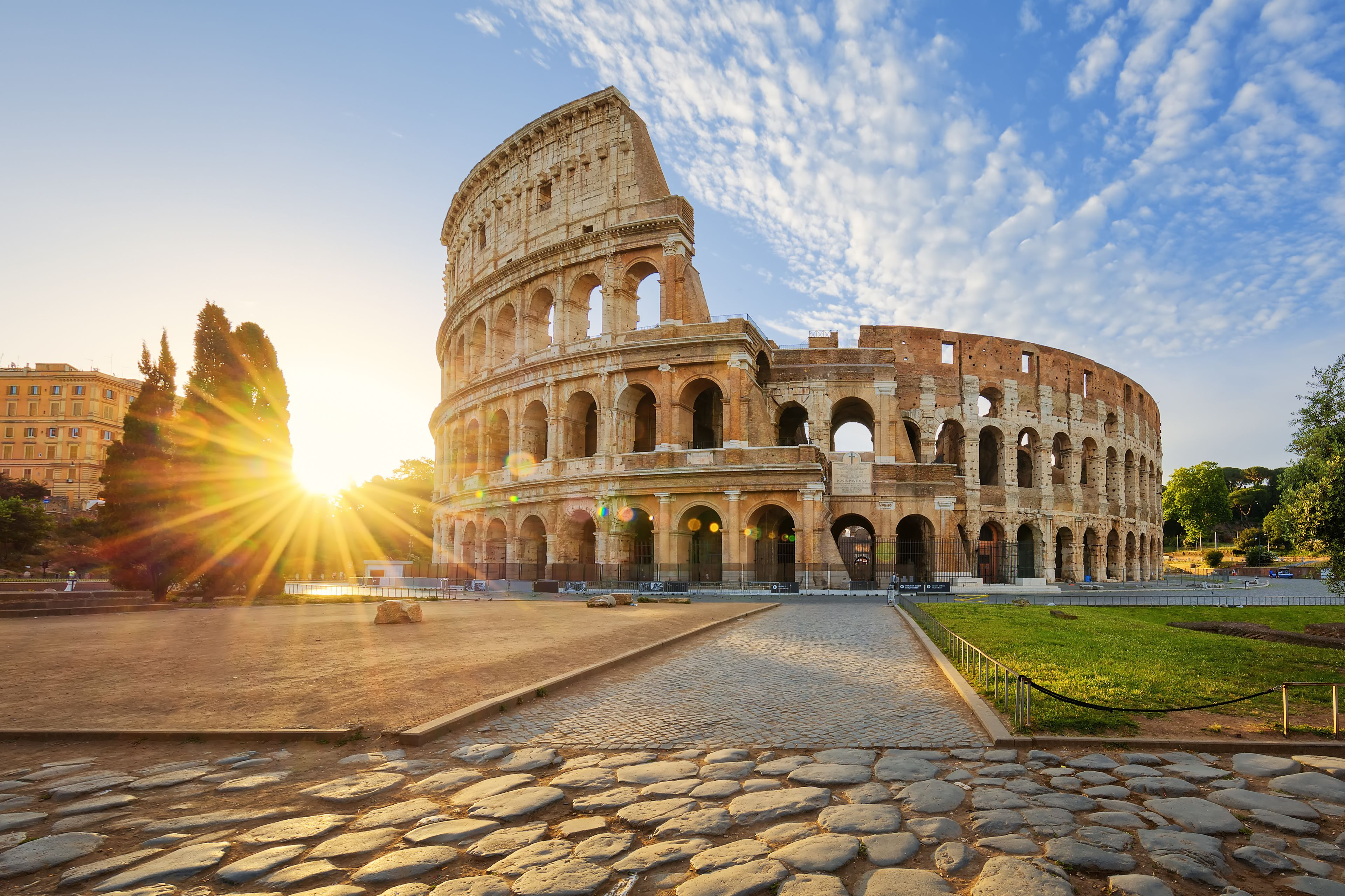 exterior of Roman colosseum with sun rising