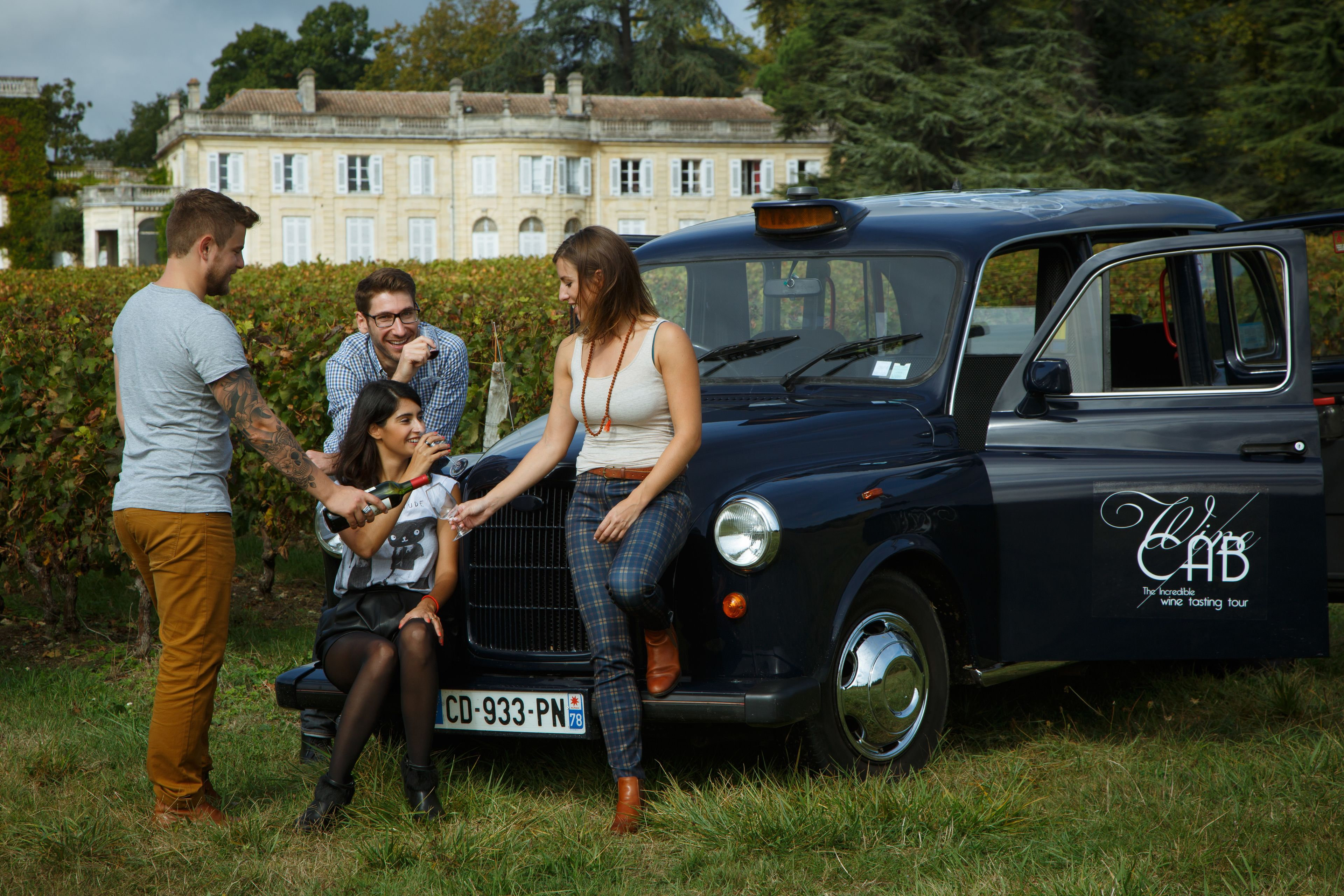 Four young people drinking wine on the hood of a wine cab in France