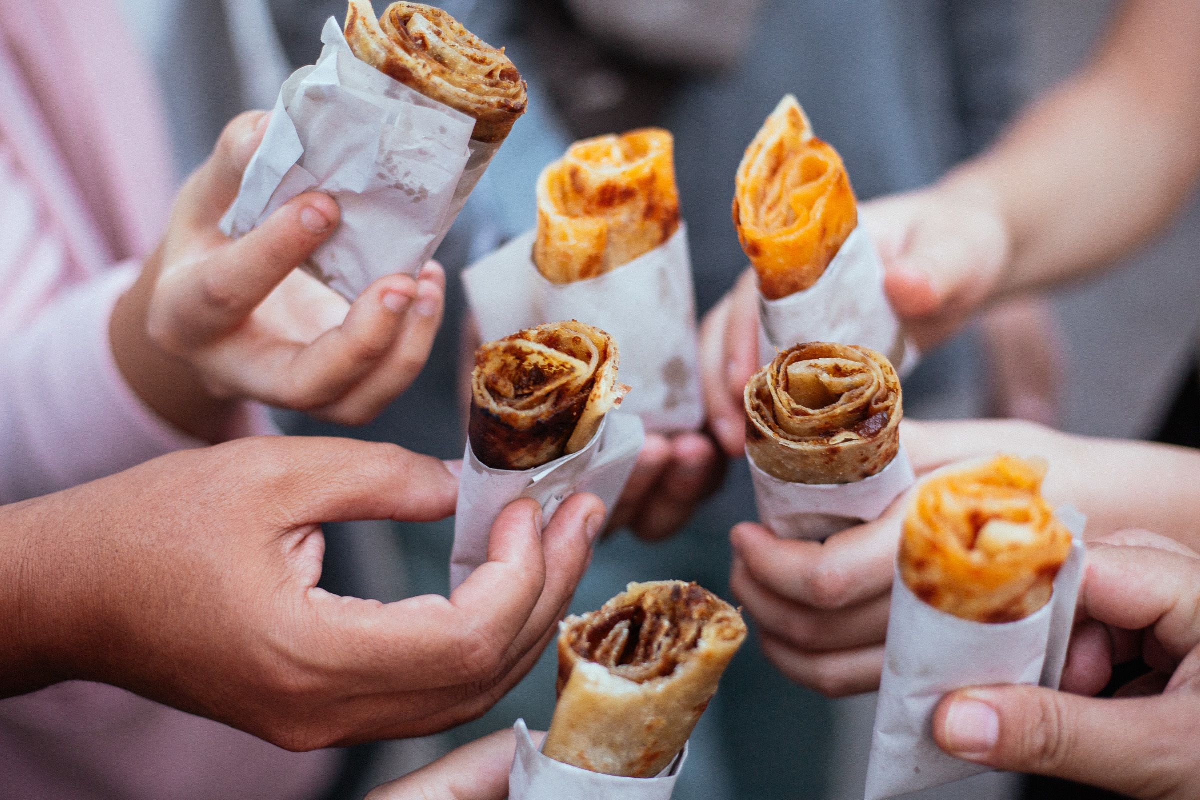 Group of people holds a wrap of street food in Marrakech
