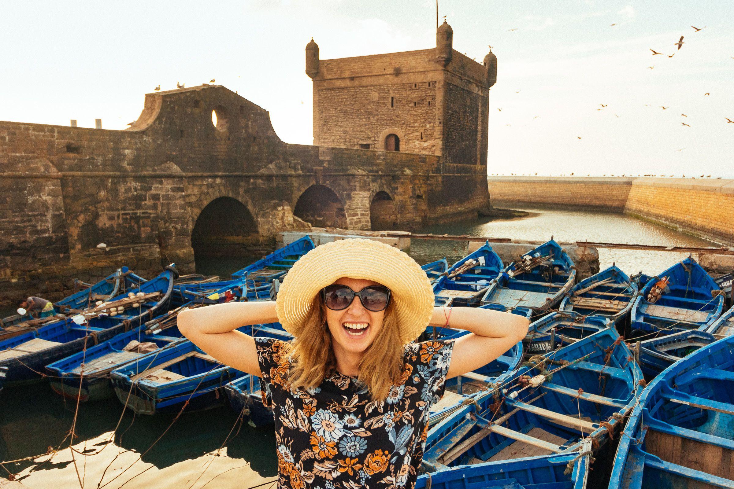 Woman posing next to boats in Essaouira