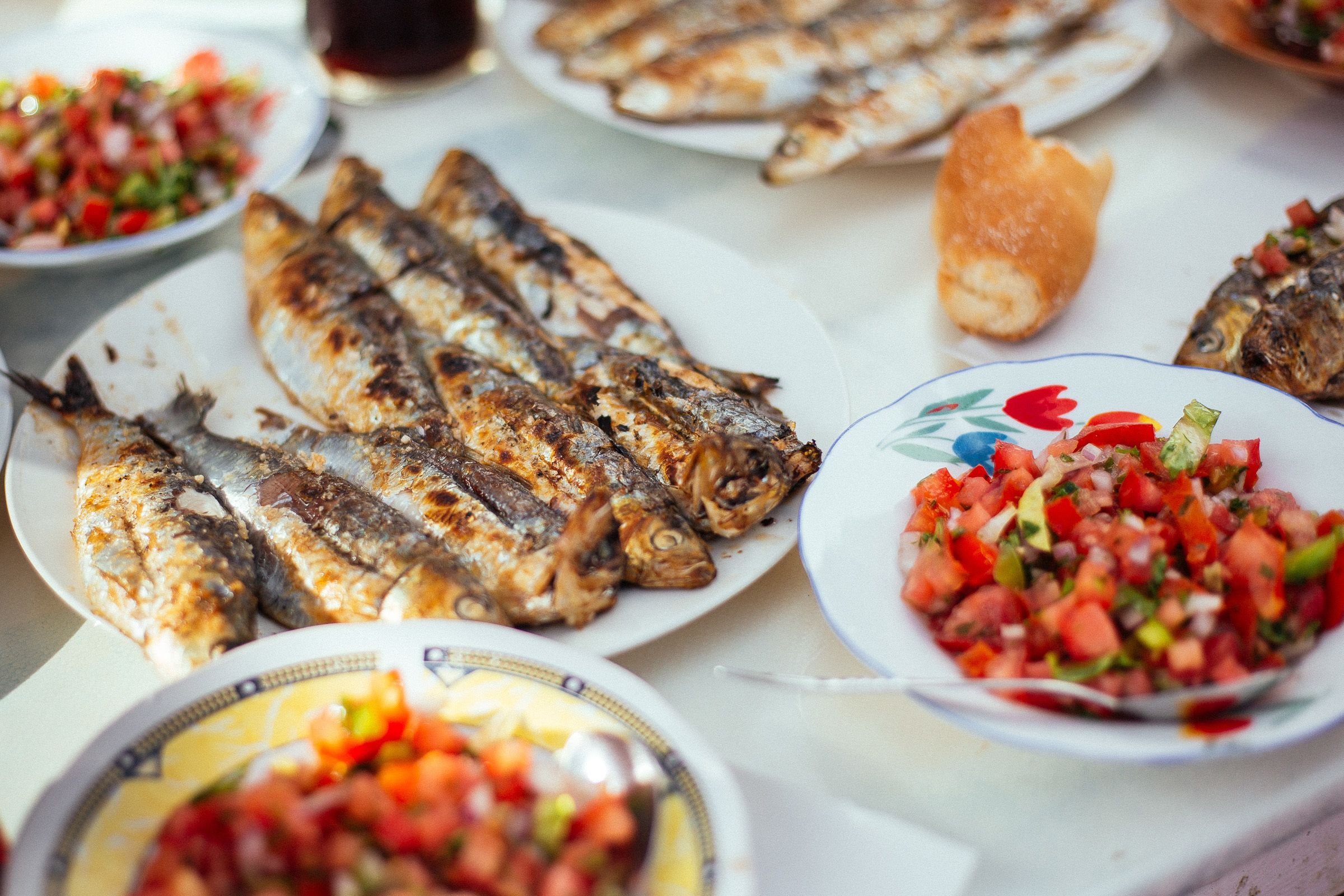 Table of cooked fish and bowls of chopped vegetables