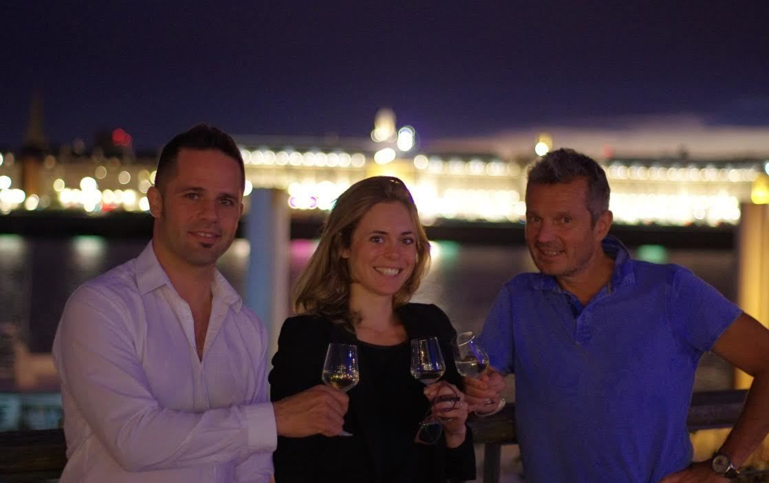Three people hold up white wine in Bordeaux at night