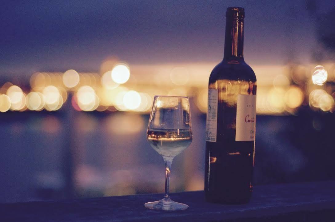 Glass of wine with city lights in the background