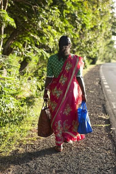 Charger l'élément 4 sur 10. Woman walking alongside a road in Mauritius