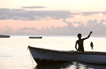 Young man on a boat holding up a caught fish in Mauritius