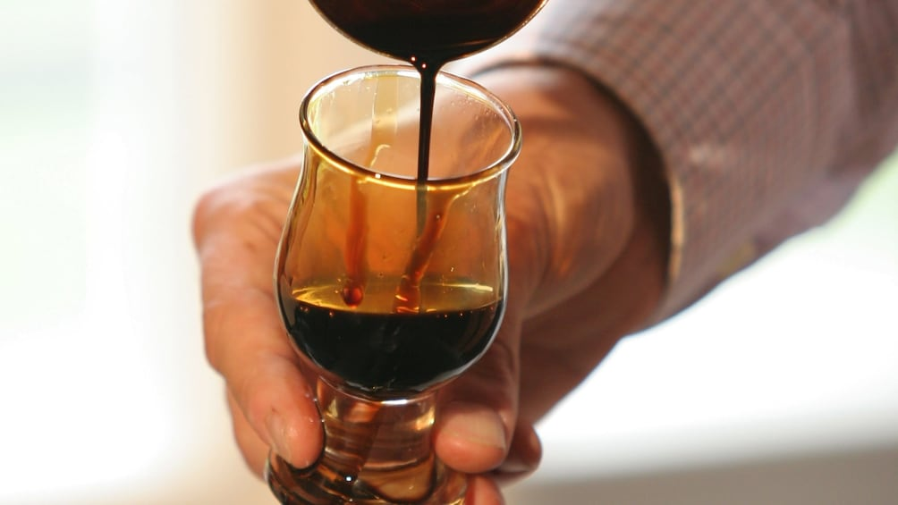 Show item 4 of 6. Man pouring balsamic vinegar into a glass on a tour in Modena