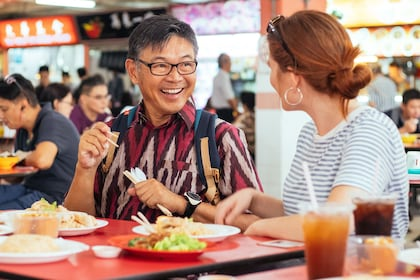 Woman and man enjoying a meal at a food court in Singapore