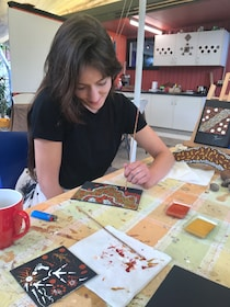 Woman painting at the contemporary Aboriginal art lesson at Janbal Aboriginal Art Gallery in Mossman