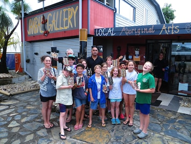 Group holding artwork in front of the Janbal Aboriginal Art Gallery in Mossman