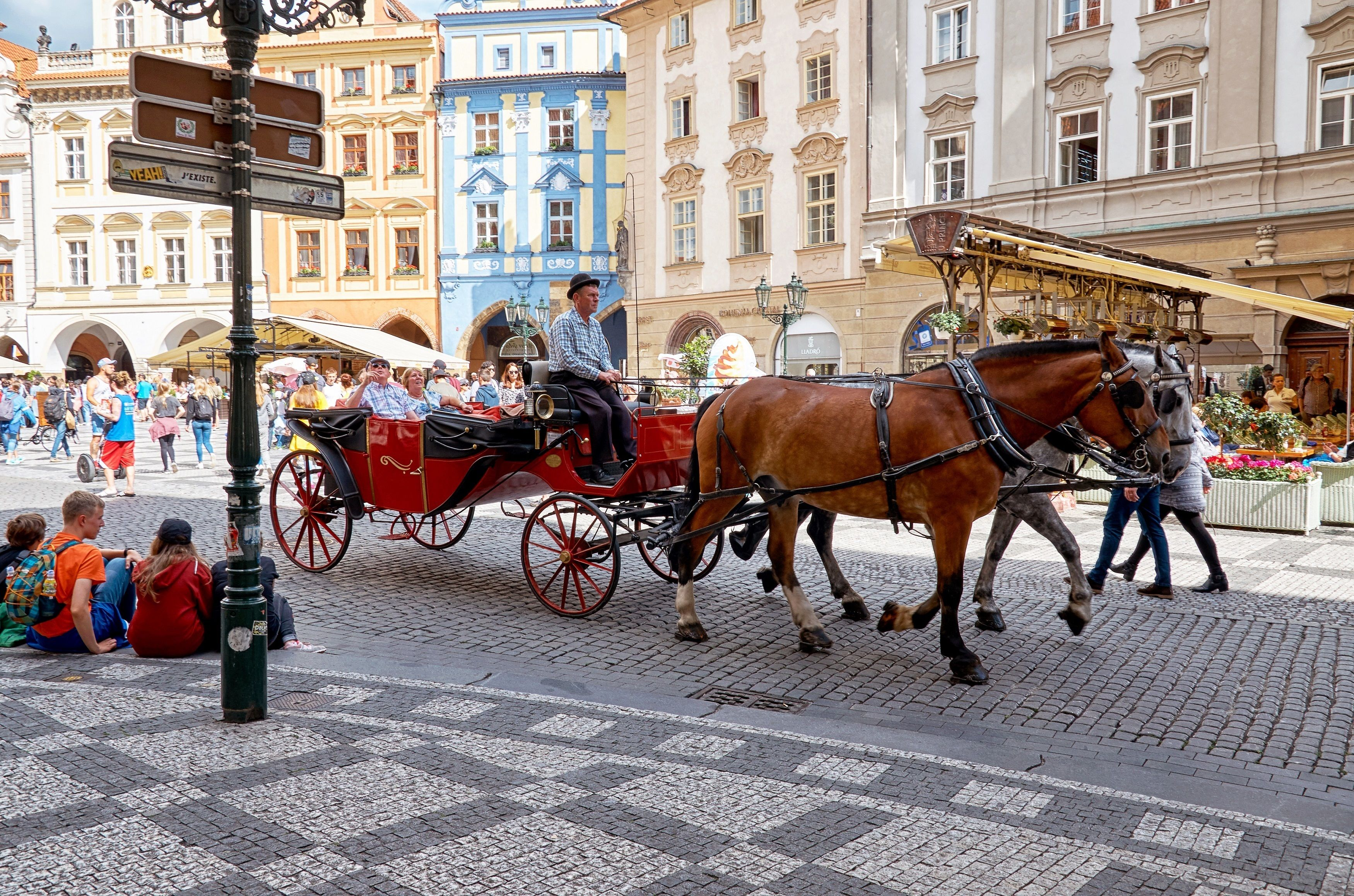 Guests on a horse drawn carriage on the streets of the Old Town Square in Prague