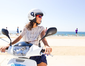 Woman on a scooter next to the beach