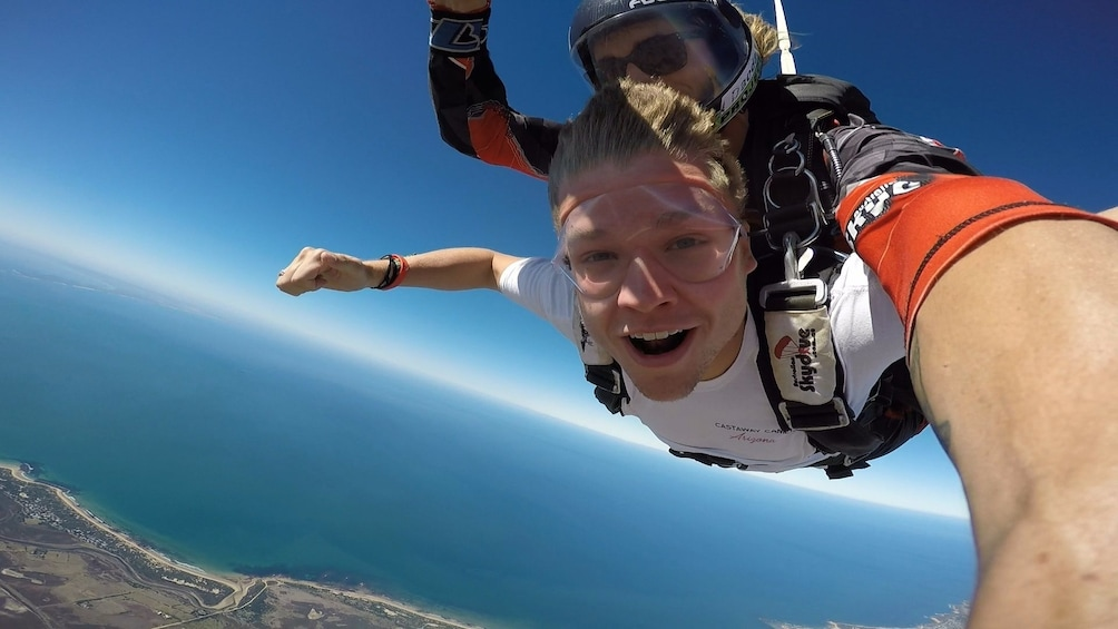 Show item 5 of 6. Guests smiling on the tandem skydive over Bells Beach, Torquay